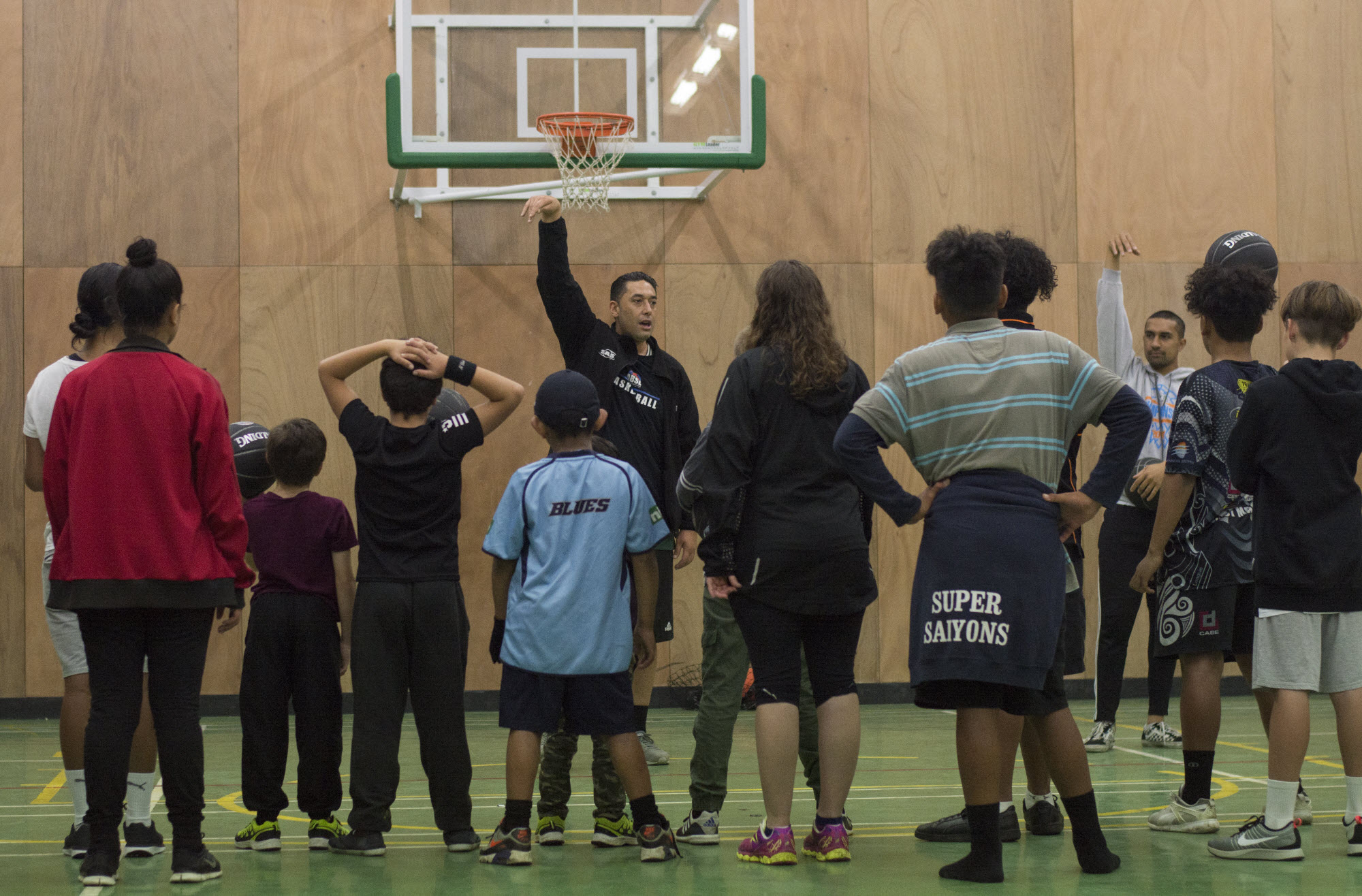 Children of different ages learning basketball